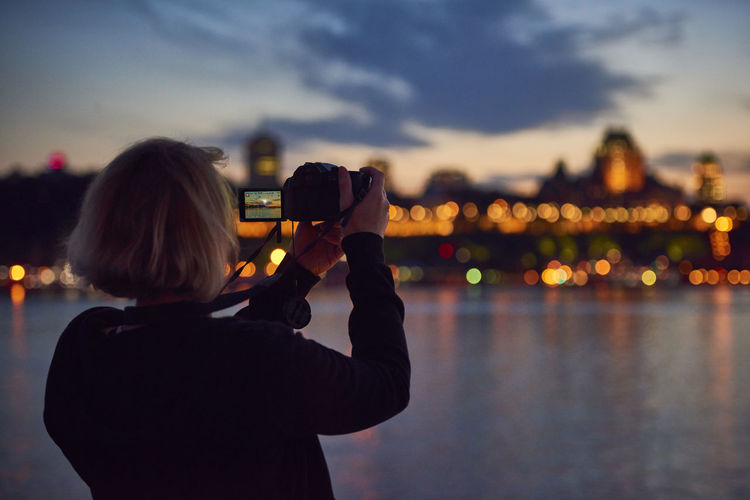 Rear view of woman photographing illuminated cityscape at sunset