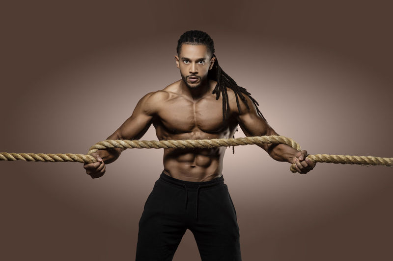 Portrait Of Athlete Exercising With Rope Against Brown Background