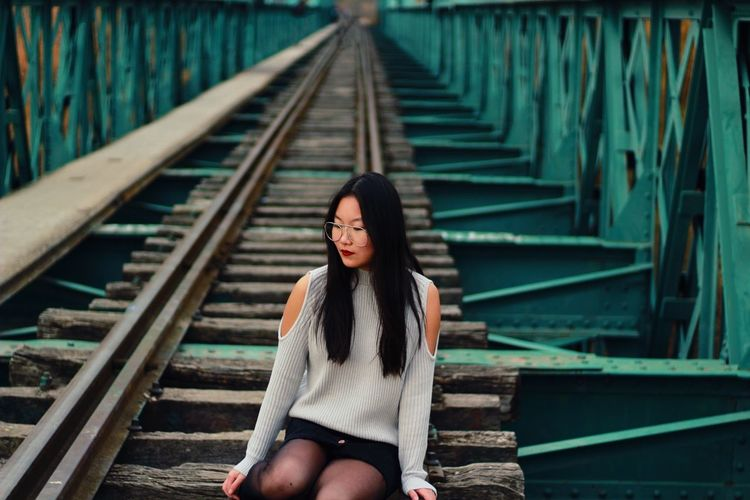 Young Woman Sitting On Railroad Tracks