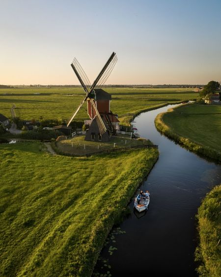 Traditional windmill in farm against sky