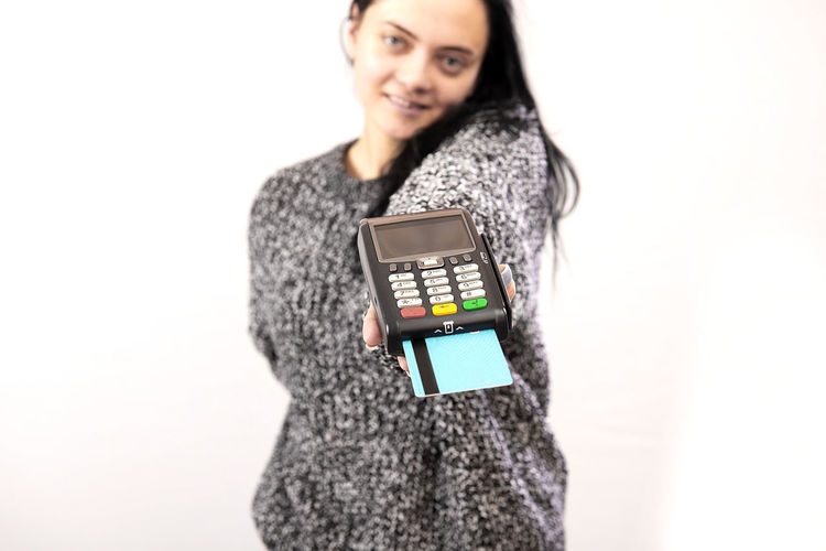 Portrait of woman holding smart phone while standing against white background