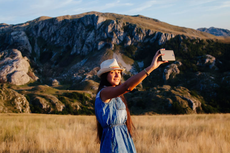 woman taking photo on phone in mountain at countryside. travel wild nature. Woman wearing casual travelling with smartphone. Beautiful Casual EyeEm Best Shots Females Hat Relaxing Travel Travel Photography Traveling Travelling Woman Beautiful Woman Casual Clothing Countryside Forest Lake Leisure Activity Lesiure Activity Mountain Photographing Relaxing Moments Selfie Smart Phone Travel Destinations Woman Portrait
