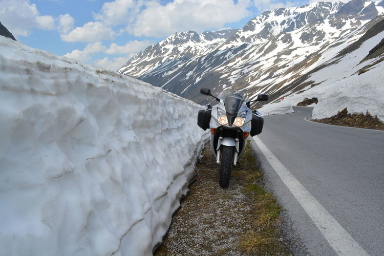 Motorcycle parked on roadside by snow retaining wall
