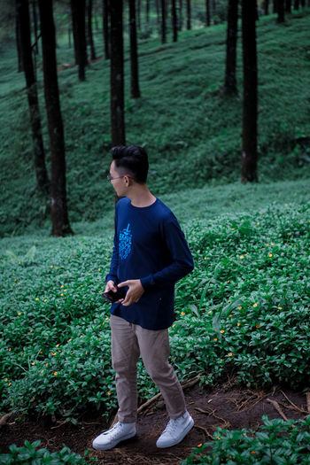 Man standing against trees and plants in forest 3