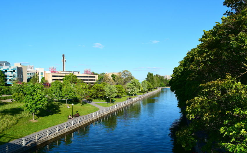 Architecture Blue Building Exterior Built Structure Canal City Day Development Green No People Ottawa University Outdoors Rideau Canal River Riverbank Scenics Sky Summer Tranquil Scene Tranquility Travel Destinations Tree University Of Ottawa Water Waterfront