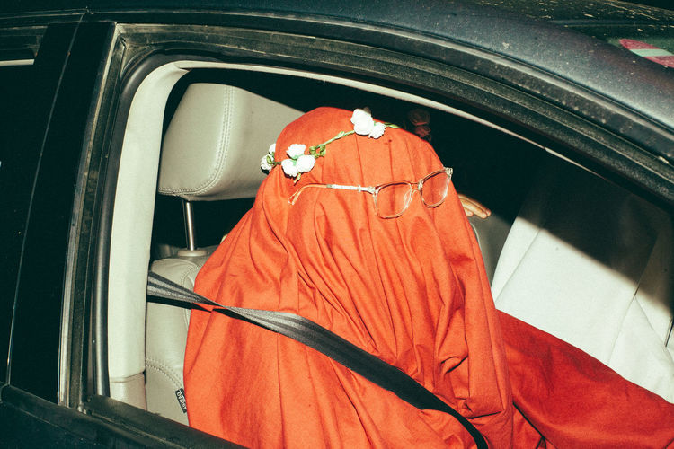 Person covering face sitting in car