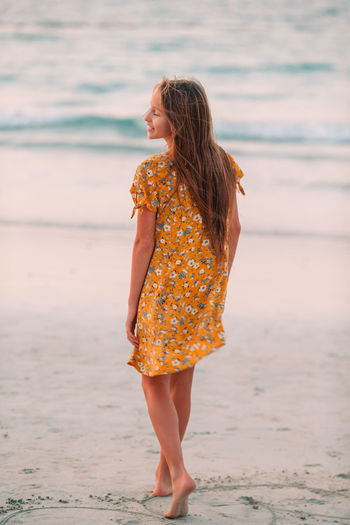 Woman looking away while standing on beach
