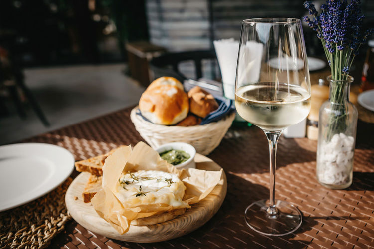 Glass of cold white wine and oven baked camembert cheese