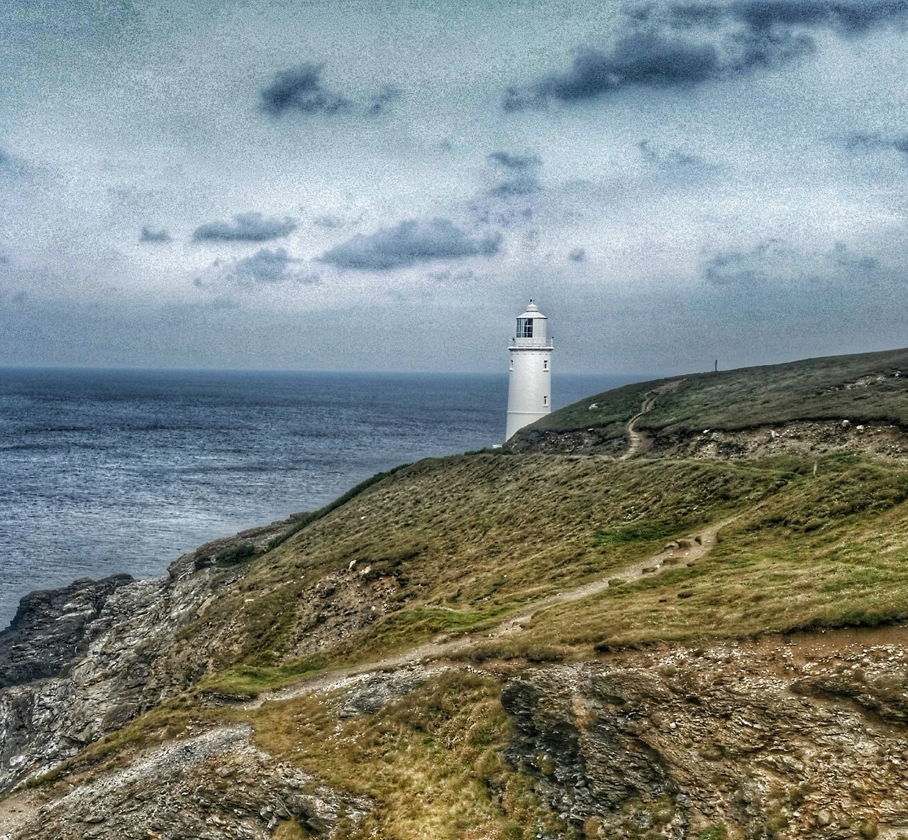 lighthouse, direction, guidance, safety, sea, sky, built structure, building exterior, architecture, nature, water, horizon over water, day, protection, scenics, cloud - sky, tranquil scene, beauty in nature, tranquility, grass, outdoors, beach, no people