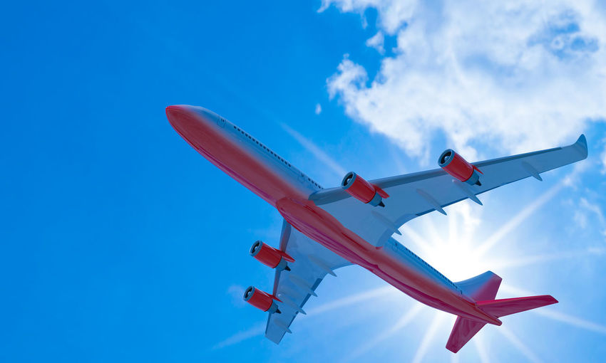 Passenger plane white red stripes flying in the sky on a bright blue day, white clouds.