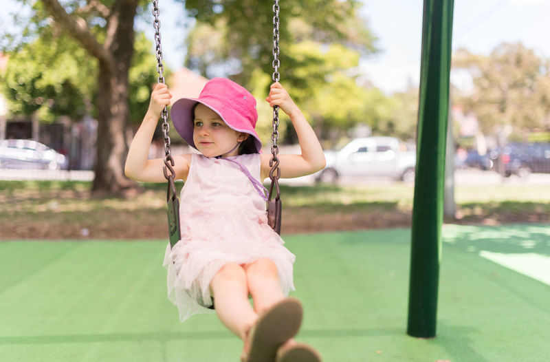 Girl playing with swing in park
