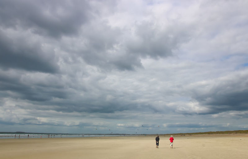 Rear view of friends walking on sand against cloudy sky at beach