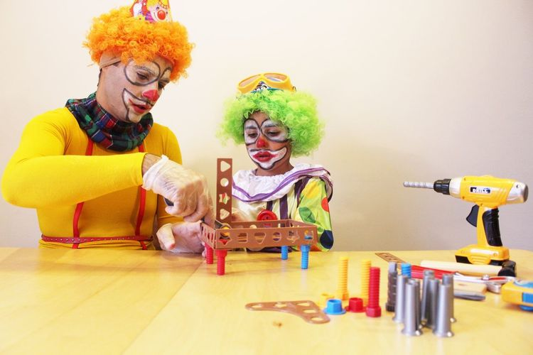 Father With Son In Clown Costume Arranging Plastic Blocks At Home