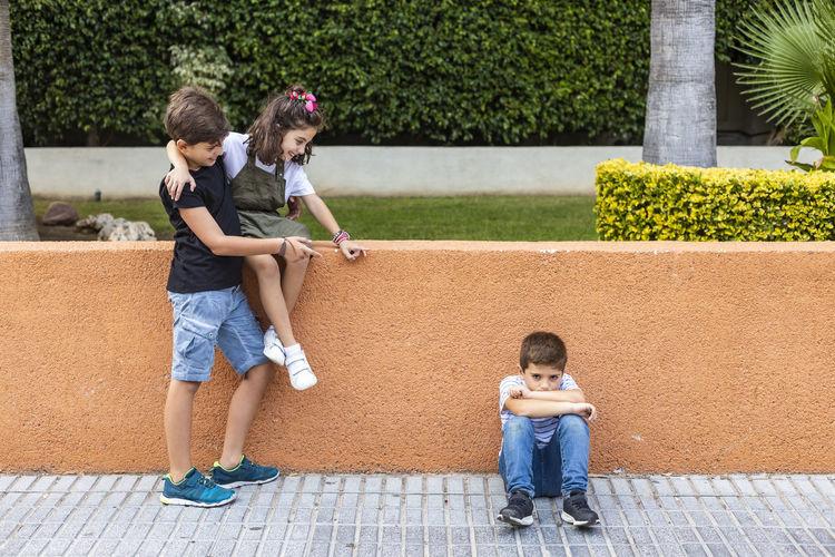 People bullying boy on footpath