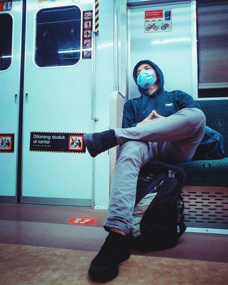 Full length of man sitting at train