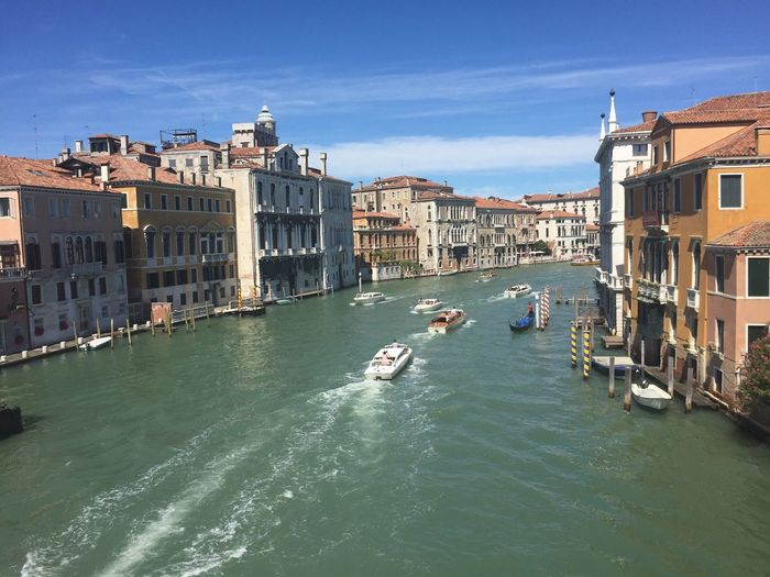 Boats in grand canal amidst buildings against sky