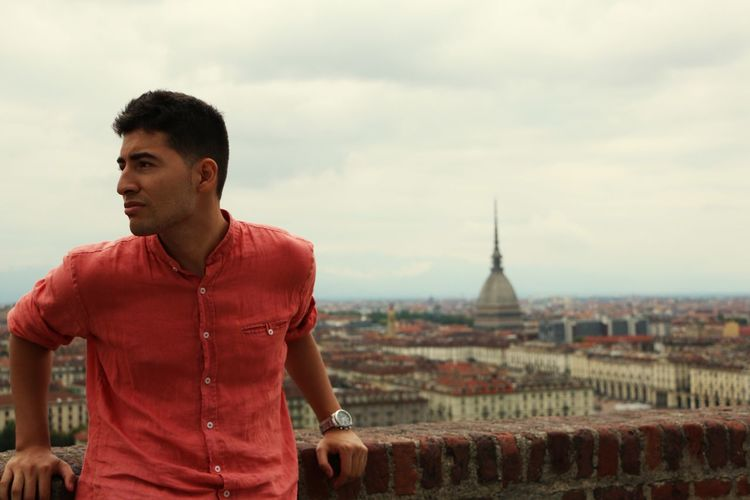 Young man leaning on brick wall against la mole antonelliana in city