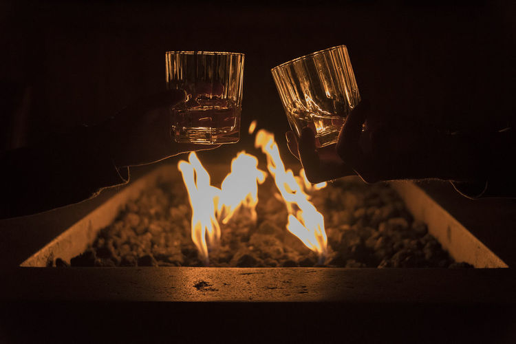 Cropped Hands Of Couple Toasting Scotch Whiskey Glasses By Bonfire