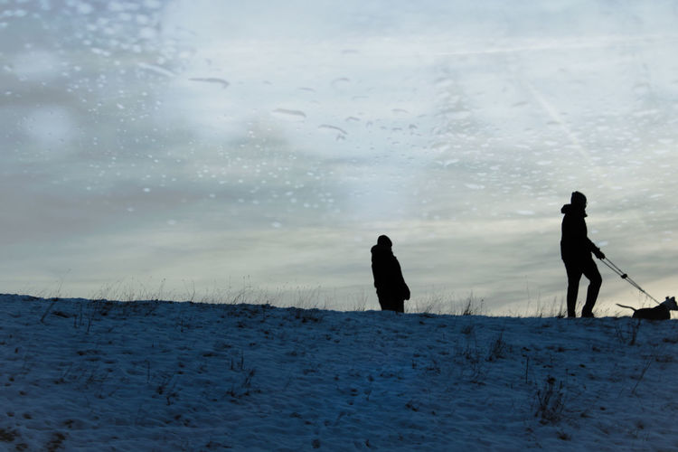 Silhouette people walking on snow covered land against sky