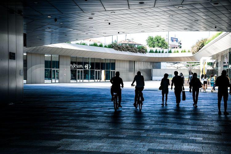 Group of people walking on tiled floor in building