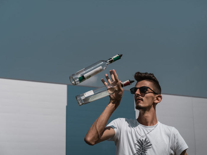 Young man playing with bottles against sky