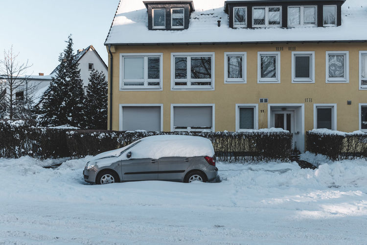 Car on snow covered house against building