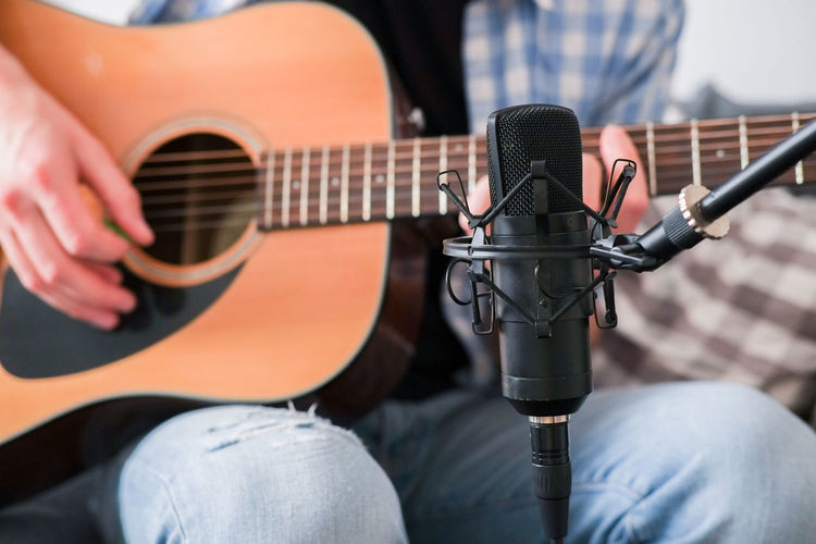 Musician recording acoustic guitar with condenser microphone in the foreground Music Musical Instrument Guitar Guitarist Guitar Player Guitar Recording Microphone Condenser Micropohn Recording Studio Home Recording Musical Equipment Artist Sitting Studio Musician Acoustic Guitar Strumming Analogue Sound