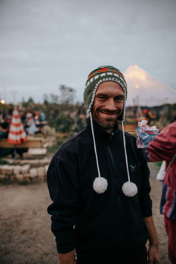 Photo of smiling man who is wearing a peruvian wool cap to keep warm at a outdoors music festival Clothing Standing Facial Hair Incidental People Men Front View Young Adult Beard Leisure Activity Real People Looking At Camera Knit Hat Focus On Foreground Young Men Lifestyles People Warm Clothing Portrait Smiling Outdoors Wool Funny Smile Autumn Wool Cap