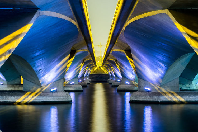 Water reflection under the bridge at night Architecture Blue Bridge Bridge - Man Made Structure Connection Diminishing Perspective Illuminated Lighting Equipment Long Low Angle View Motion No People Reflection Transportation Underneath Water