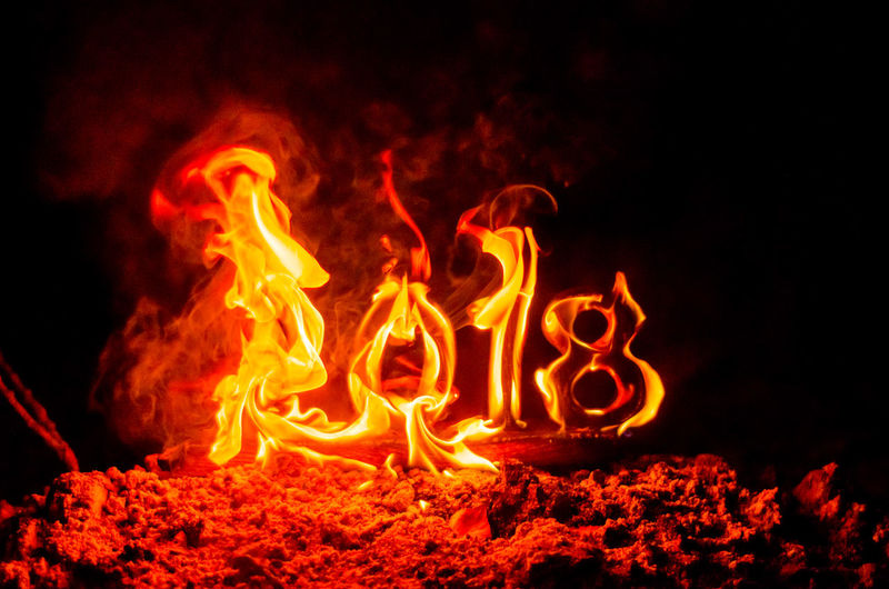 Wooden figures 2018 are burned in a flame. Conceptual photo end of the year. NewYear Black Background Bonfire Burning Close-up Communication Environment Fire Fire - Natural Phenomenon Flame Glowing Heat - Temperature Illuminated Land Long Exposure Motion Nature Night No People Oldyear Orange Color Outdoors Capture Tomorrow