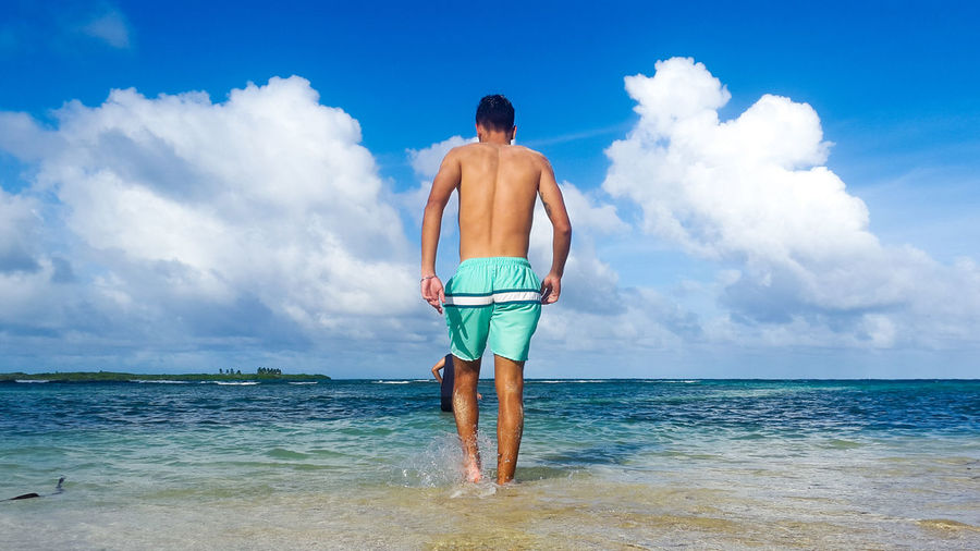 Rear View Of Shirtless Man Wading In Sea Against Sky