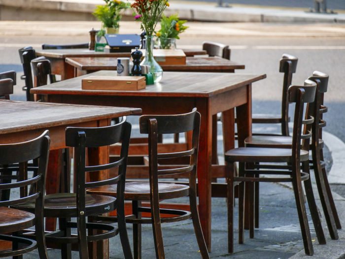 URBANANA #urbanana: The Urban Playground Restaurants Absence Arrangement Available Light Brown Business Cafe Chair Day Empty Focus On Foreground Furniture In A Row Indoors  No People Plant Restaurant Seat Setting Sidewalk Cafe Streetphotography Table Wood - Material