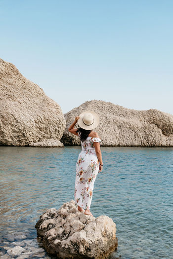 Rear view image of woman in long summer dress standing on rock on beautiful beach.