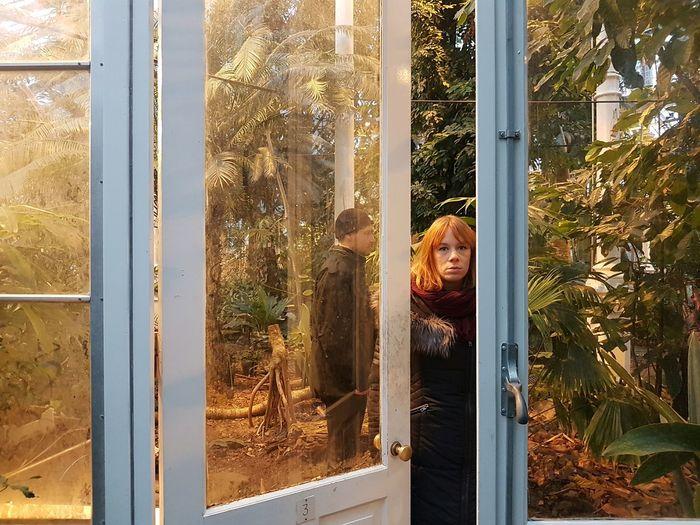 Man and woman in greenhouse seen through door
