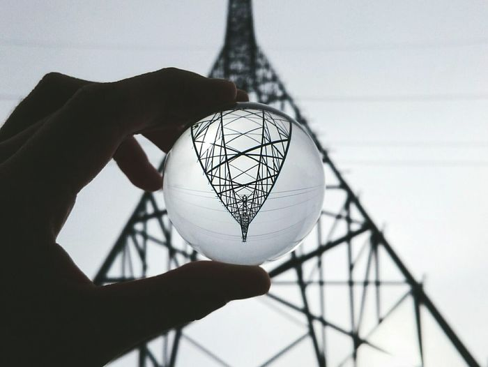 Cropped Silhouette Hand Holding Crystal Ball With Electricity Pylon Reflection