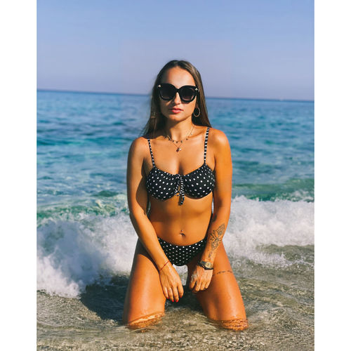 Young woman wearing sunglasses at beach against sky