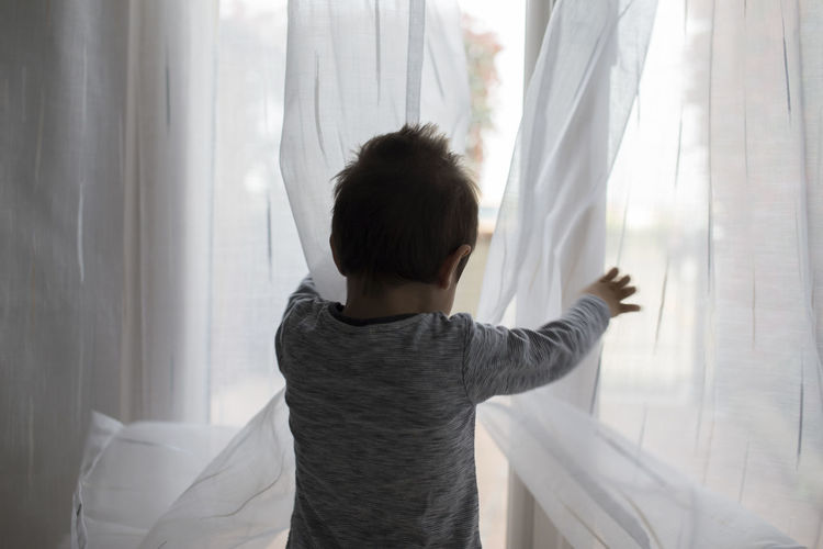 Rear view of boy standing by curtain at home