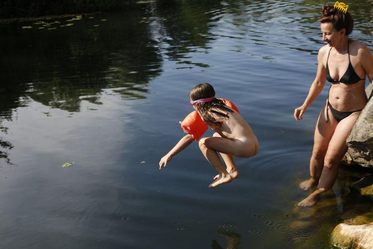Full length of shirtless boy in lake