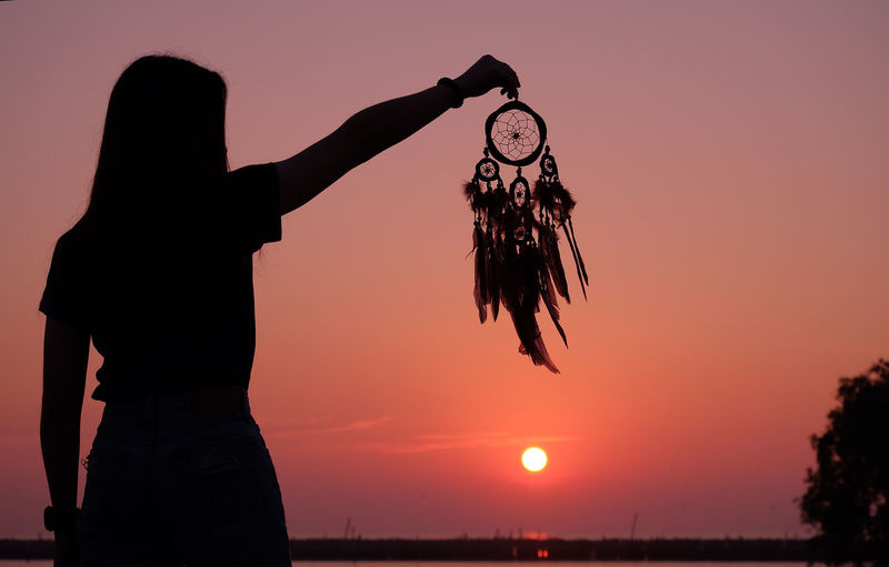 Woman holding dreamcatcher against sky during sunset