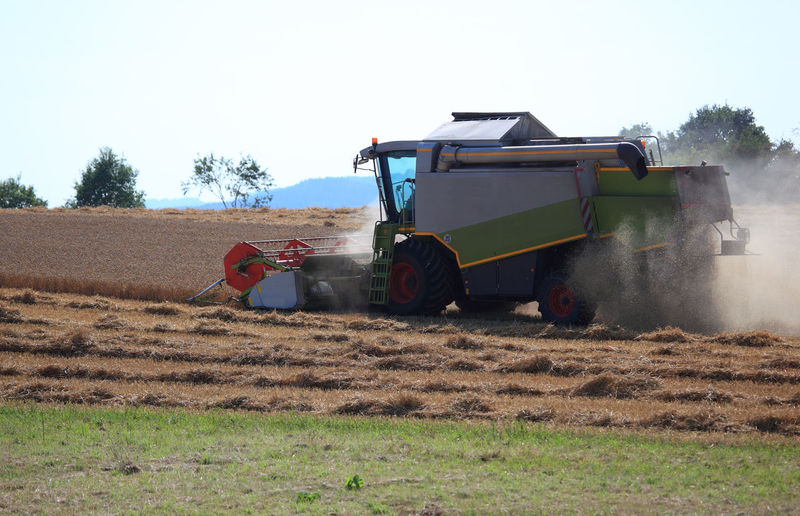 harvester during wheat harvest on a dry dusty field Agricultural Equipment Agricultural Machinery Agriculture Combine Harvester Day Dust Environment Farm Field Harvesting Land Land Vehicle Landscape Machinery Mode Of Transportation Nature Outdoors Plant Rural Scene Sky Tractor Transportation