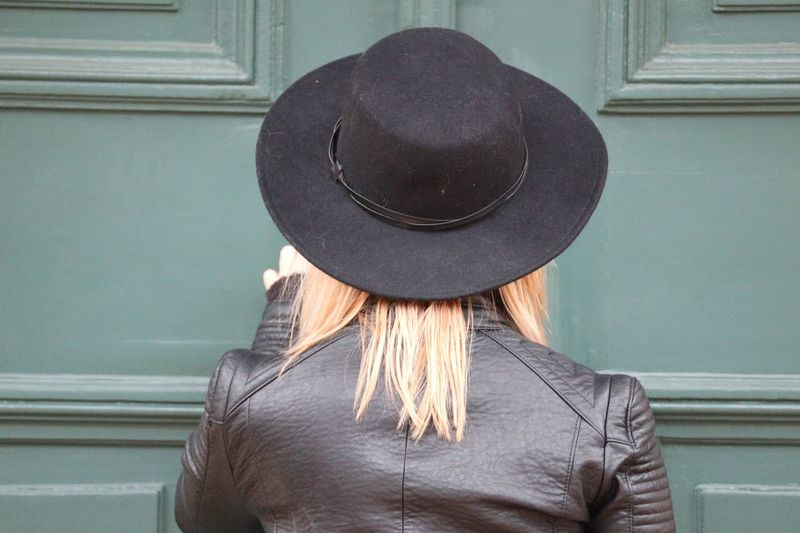 Rear View Of Woman Wearing Hat Against Closed Door