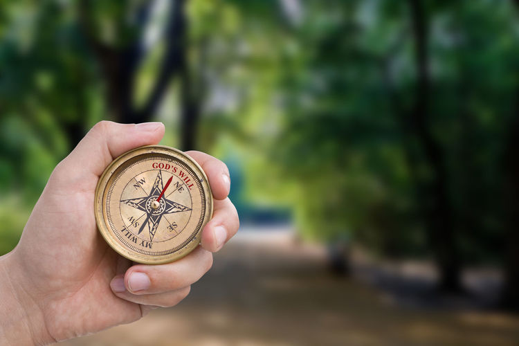 Male Hand Holding Compass - GOD's Will Male Hand Fingers Holding Compass Direction Christianity Religion Faith Navigation Lost Guidance Counsel Path Forest Trees Followme Wisdom Green Crossroads Route Way Preparation  Nature Inspire God's Will