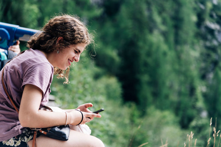 Beautiful young woman sitting texting on smartphone in nature Nature Sitting Adult Adults Only Casual Clothing Day Focus On Foreground Girl Holding Human Hand Leisure Activity Lifestyles Nature One Person Outdoors People PhonePhotography Real People Sitting Smartphone Texting Tree Wireless Technology Women Young Adult Young Women