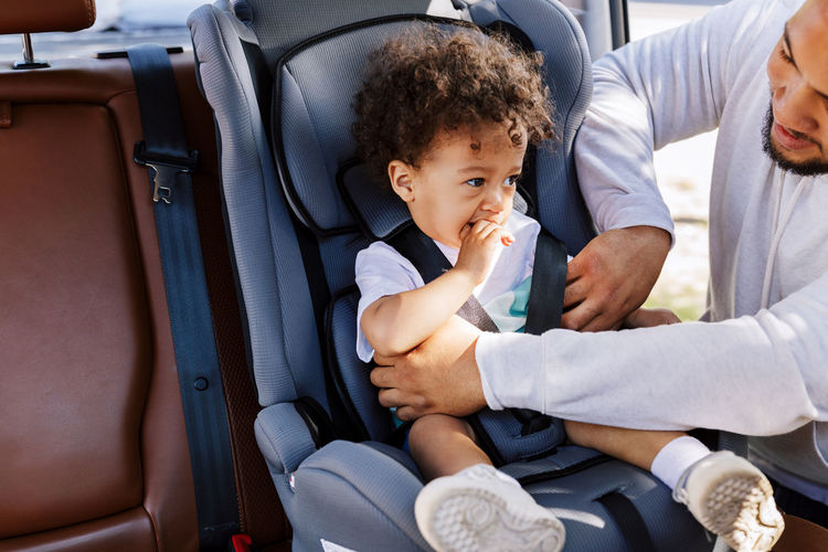 Man with toddler son sitting on seat in car