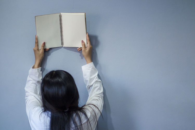 Rear view of woman reading book