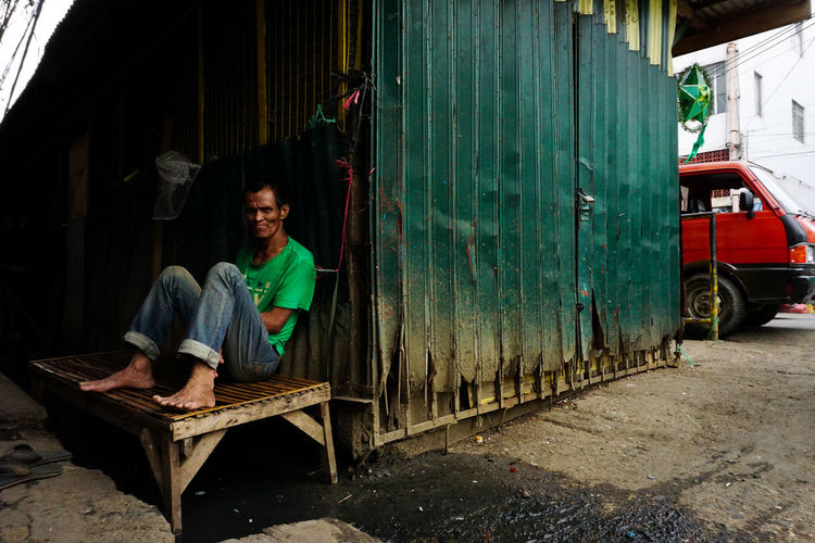Portrait Of Mature Man Sitting On Dirty Bench By Container
