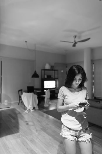 Woman looking at camera while standing at home