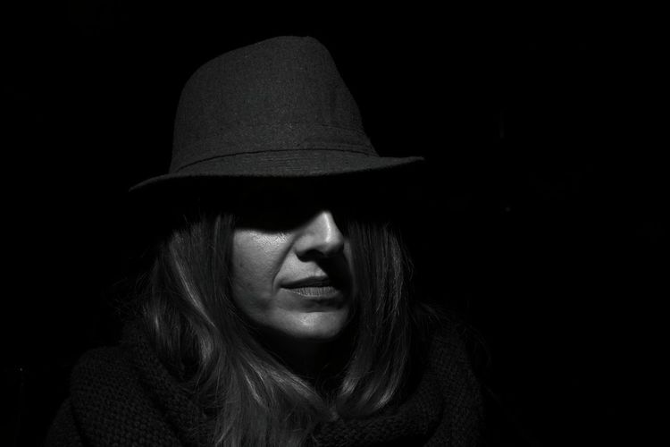 Close-Up Of Woman Wearing Hat Against Black Background