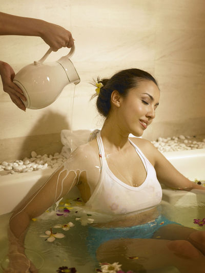 Cropped Hand Of Person Pouring Milk On Woman In Bathtub
