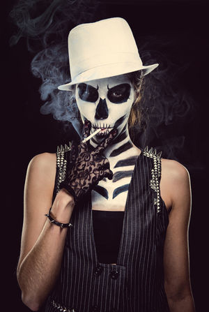 Woman with skeleton face art smoking over black background, conceptual photo Black Background Cancer Day Of The Dead Death Halloween Horror Looking At Camera Make-up Makeup Skeleton Smoke Smoking Tobacco Woman Bad Habit Body Arts Cigarette  Concept Conceptual Face Art One Person Skull Studio Shot Young Adult